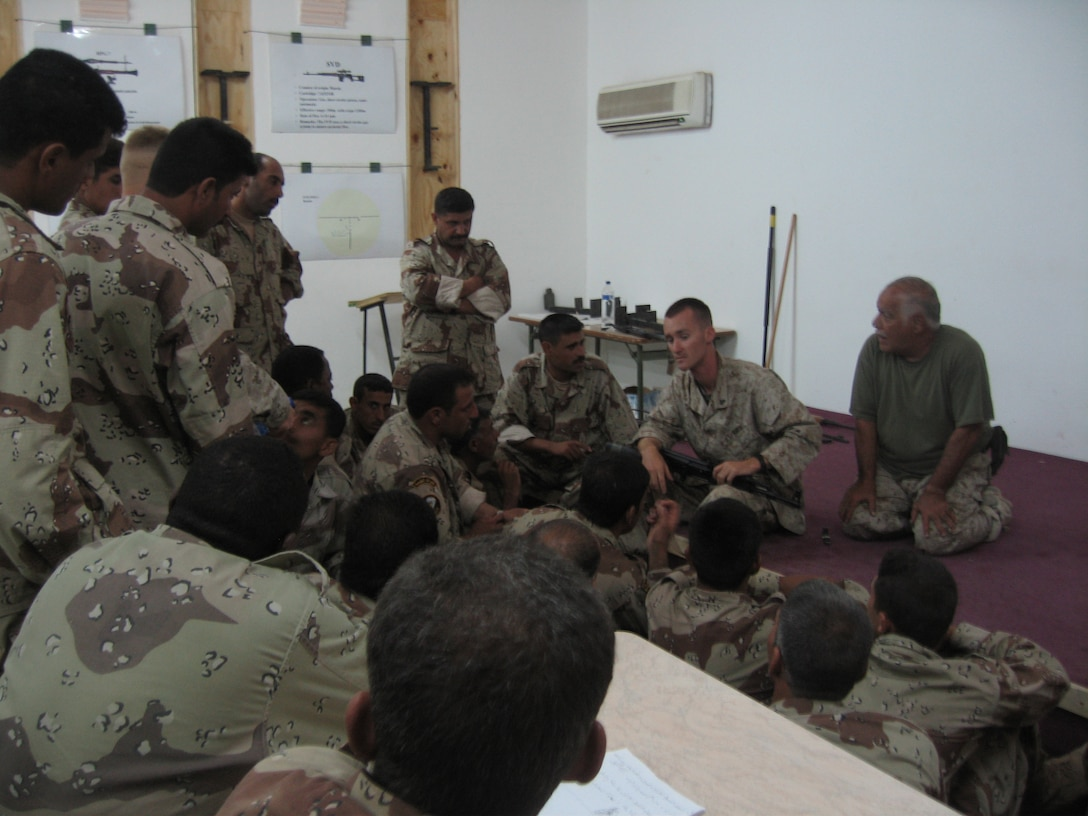 CAMP HABBANIYAH, Iraq - Corporal Russell R. Hall, a wire man with the 2nd Marine Division Training Center, gives a class on the AK-47 to Iraqi Soldiers during the Iraqi Small Arms Weapons Instructors Course held here. Hall is responsible not only for maintaining the units telecommunications system but for assisting with the instruction of Iraqi Security Force personnel who attend various courses here.