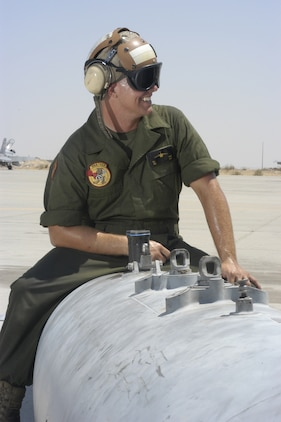 Pfc. Kevin Butters, an engine mechanic with VMA-223 who is preparing to deploy to Iraq for the first time, sweats as he holds steady a 300-gallon aero-fuel storage tank before placing in onto a AV-8B Harrier.