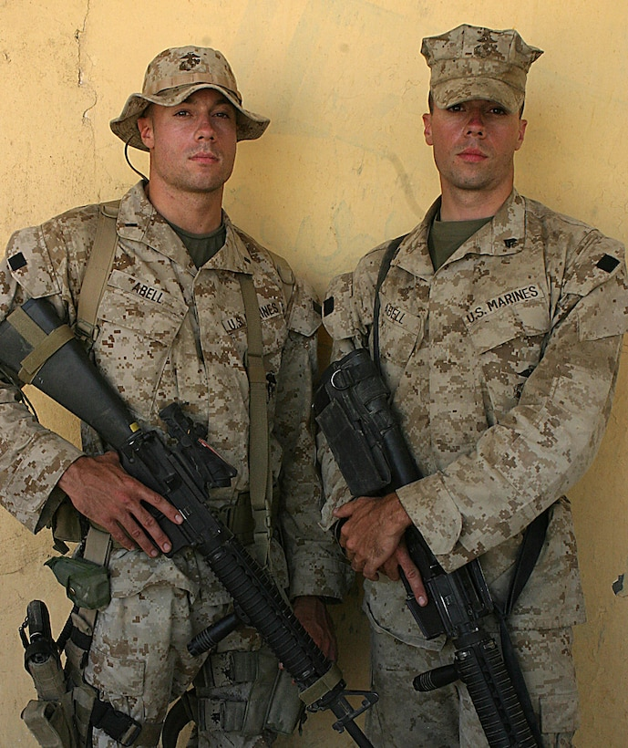 CAMP HIT, Iraq (Sept. 14, 2005)  - First Lieutenant Bryan J. Abell (left), the Scout Sniper Platoon leader for 3rd Battalion, 1st Marine Regiment, and Cpl. Jason P. Abell, a machine gunner with 3rd Battalion, 25 Marines, both of Demasses, Md. cross paths here as they trade places in Iraq. (Official Marine Corps photo by Cpl. Adam C. Schnell)