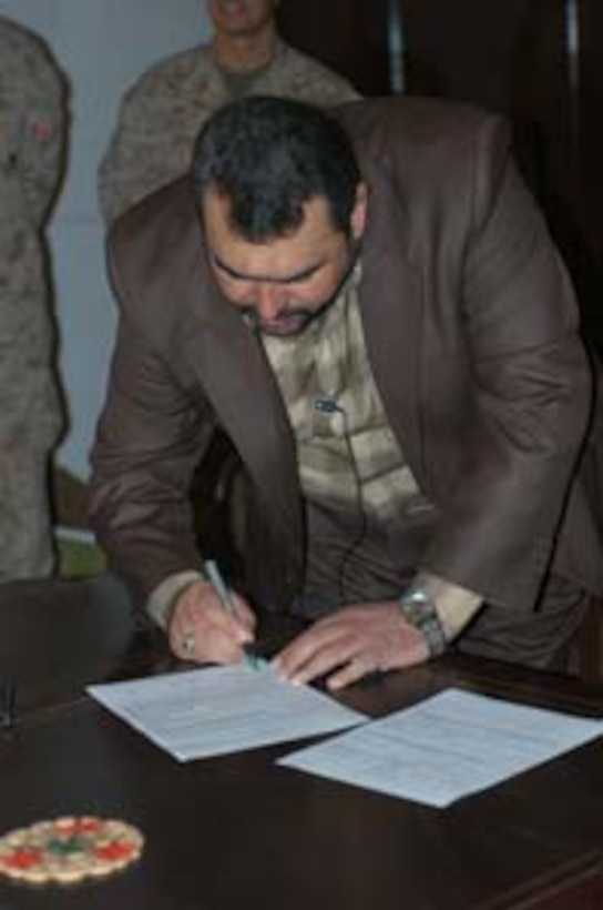 The governor of Iraq?s Al Anbar province, Ma?amoun Sami Rasheed, signs a $2.6 million contract to supply, connect and install five water treatment plants throughout the province here Nov. 23.