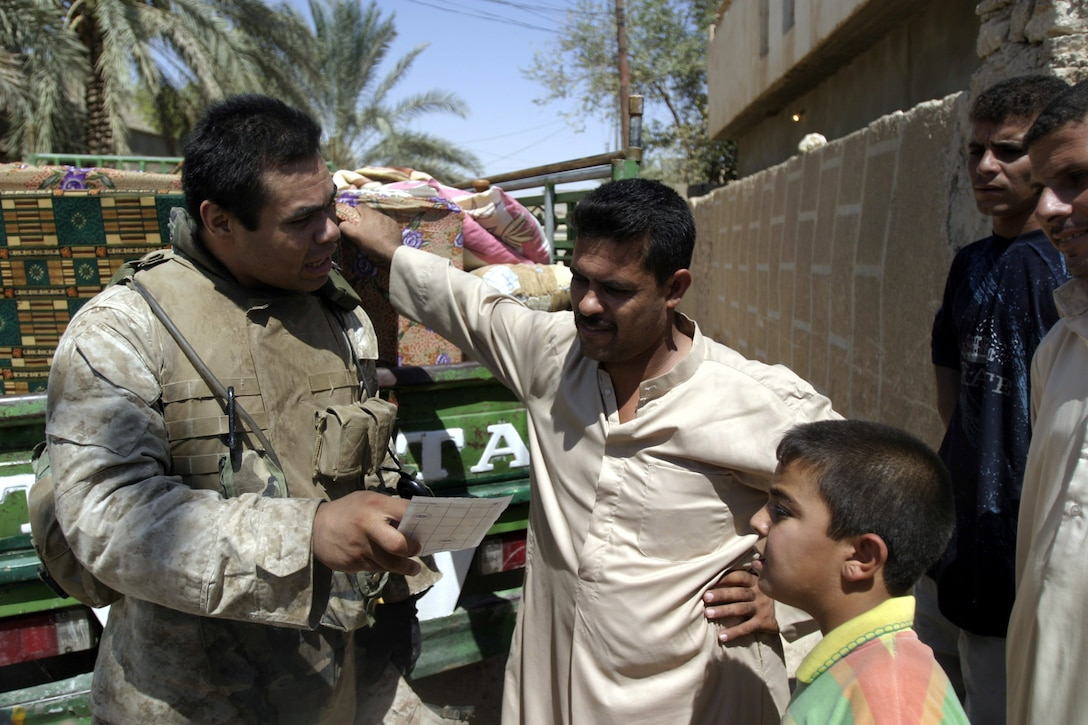 """Hit, Al Anbar, Iraq (July 22, 2005)--Greenport, N.Y. native, Sgt. Oscar F. Aguilera, a 24-year-old squad leader with 4th platoon, Company """"K"""", 3rd Battalion, 25th Marine Regiment shows an Iraqi man a picture of a friend's family in order to show that they all had families and loved and continued to dangerous jobs such as this. (Official USMC Photo by Corporal Ken Melton)"""