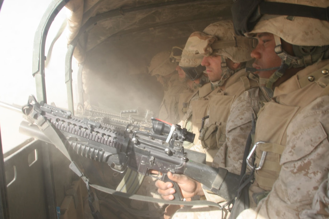 Marines with 1st Platoon, Company L, 3rd Battalion, 2nd Marine Regiment, Regimental Combat Team-2 watch the side streets of the city as they roll into the city during a mission here to capture high value individuals and disrupt insurgent activity in the city. The Marines captured 26 detainees during the half-day operation.