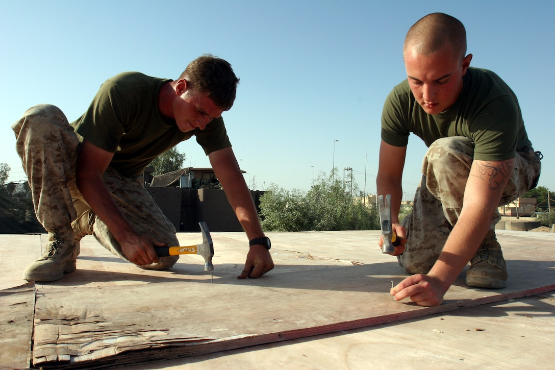 AR RAMADI, Iraq (September 25, 2005) - Corporal Joseph Holloway, a combat engineer from 1st Combat Engineer Battalion, and Lance Cpl. Jason Smither, a infantryman from Weapons Platoon, Company L, work together to nail down a piece of the roof on a new living space for visiting members of the Iraqi Security Forces at Snake Pit Sept. 25. Photo by Cpl. Shane Suzuki.