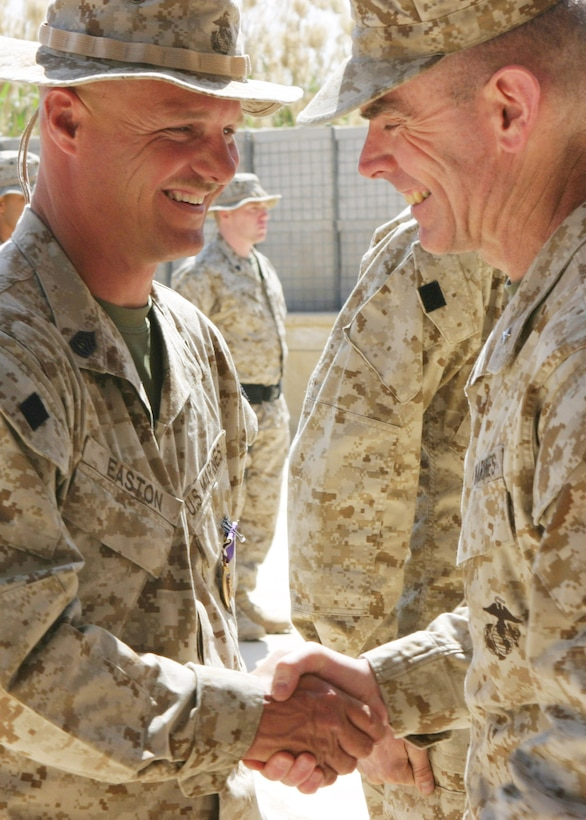 CAMP BLUE DIAMOND, Iraq - Brigadier Gen. Joseph J. McMenamin, assistant division commander for 2nd Marine Division, shakes hands with Gunnery Sgt. William Easton, staff non commissioned officer-in-charge of 2nd Light Armored Reconnaissance after he received a Purple Heart, April 8, for injuries he received from a roadside explosion.  An improvised explosive device (IED), used by insurgents as a way to inflict collateral damage from a distance, rocked through two convoys as they passed one another in opposite directions on a dirt road near the base, March 13.  Easton and his team were providing security on the road from within their Light Armored vehicles and Humvees.  U.S. Marine Corps photo by Sgt. Stephen D'Alessio (RELEASED)