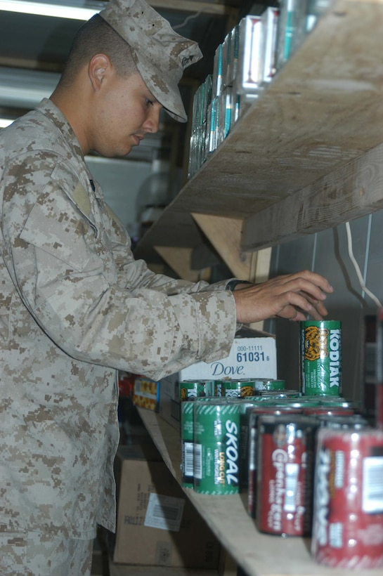 CAMP HURRICANE POINT, Ar Ramadi, Iraq (April 21, 2005) -Sergeant Miguel E. Mejia, retail store manager with Headquarters and Service Company, 2nd Force Service Support Group, 2nd Marine Division, stocks a shelf with tobacco products at the post exchange here prior to opening time. The 24-year-old Salinas, Puerto Rico native, runs the Warfighter Express Service Team, which provides exchange items for purchase, dispersing and postal services to warriors fighting on the frontlines of the urban battlefield. Each week, Mejia loads a 7-ton truck full of merchandise from the Camp Ramadi Exchange and visits Camps Snake Pit and HP where Marines with 1st Battalion, 5th Marines reside. Photo by Cpl. Tom Sloan