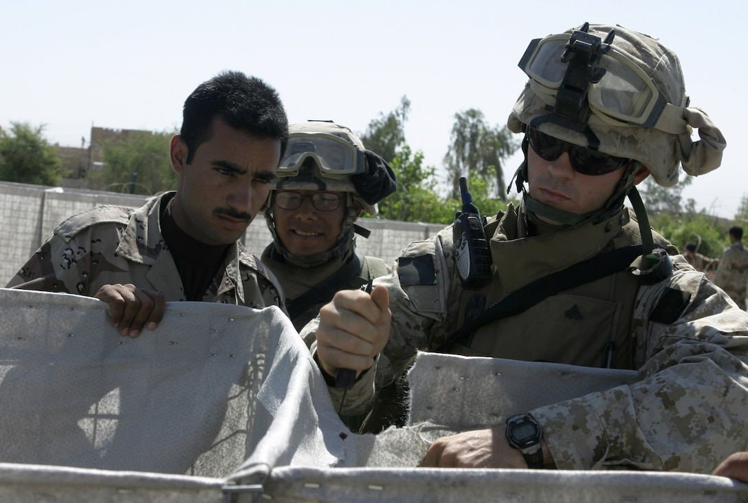 FALLUJAH, Iraq - Cpl. Allen Ryals, 2nd Squad leader, 2nd Platoon, Company A, 2nd Combat Engineer Battalion, right, cuts through the canvas of a Hesco barrier in an Iraqi soldiers' base of operations here May 26 as fellow engineer, Lance Cpl. Mario Castillo, and an Iraqi soldier, observe.  Ryals' engineers worked alongside the Iraqi soldiers to teach them how to properly fortify one of their headquarters in the city by laying out barricades and stretching out wire.