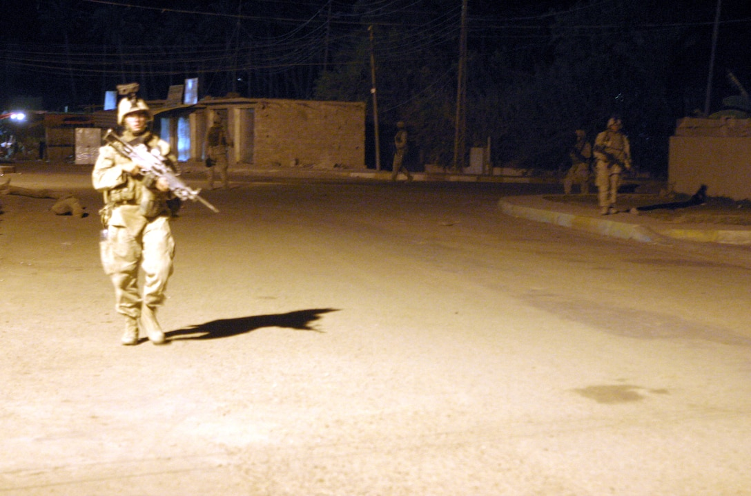SAQLAWIYAH, Iraq - Marines with 2nd Squad, 4th Platoon, Company A, 1st Battalion, 6th Marine Regiment move through the city streets here under the cover of darkness as they prepare to reach their designated search sector during 'Operation Hard Knock' July 27.  Company A Marines searched dozens of houses throughout the small township outside Fallujah, searching for weapons, explosives and insurgent activity while gathering census data on the populace there.  The unit apprehended one suspected insurgent supporter.