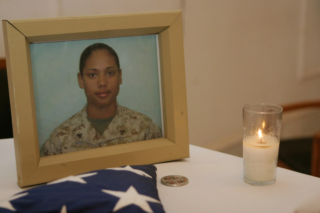 CAMP BLUE DIAMOND, AR RAMADI, Iraq - A picture, a flag and a candle adorn a tabletop in the camp's chapel in memorial to Cpl. Ramona M. Valdez a 21-year-old field radio operator and member of the 2nd Marine Division's G-6 Communications section.  Valdez was killed in when a suicide car-bomber struck her convoy a few days earlier.  U.S. Marine Corps photo by Sgt. Stephen D'Alessio (RELEASED)