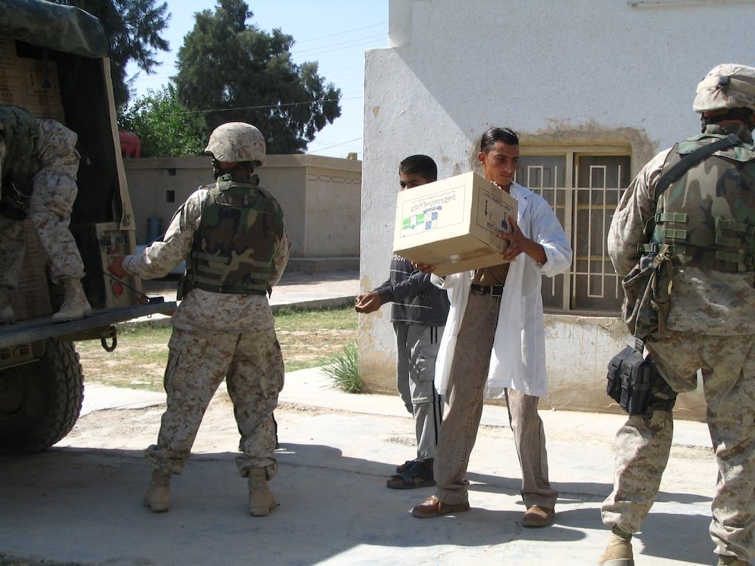 SAQLAWIYAH, Iraq - Dr. Ayad, head of the medical clinic here, helps Marines of the 5th Civil Affairs Group offload supplies from their vehicle May 29.  The civil affairs personnel distributed supplies including 3000 syringes, 36 liters of sanitizer, and 3000 surgical masks.