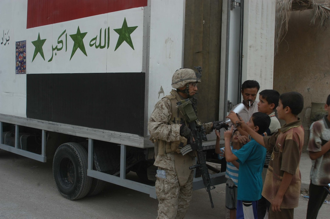 AR RAMADI Iraq (June 29, 2005) -Sergeant Joe A. Salinas, squad leader for 3rd Squad, 4th Platoon, Company B, 1st Battalion, 5th Marine Regiment, stands behind an Iraqi ice cream truck and hands out coalition forces fliers during a mission in the city here June 28. The 35-year-old from San Antonio, Texas and his fellow Marines conducted a patrol through a portion of their company's area of operations to locate enemy sniper positions. Company B's observation post has been taking sporadic sniper fire from the area around it. Photo by: Cpl. Tom Sloan