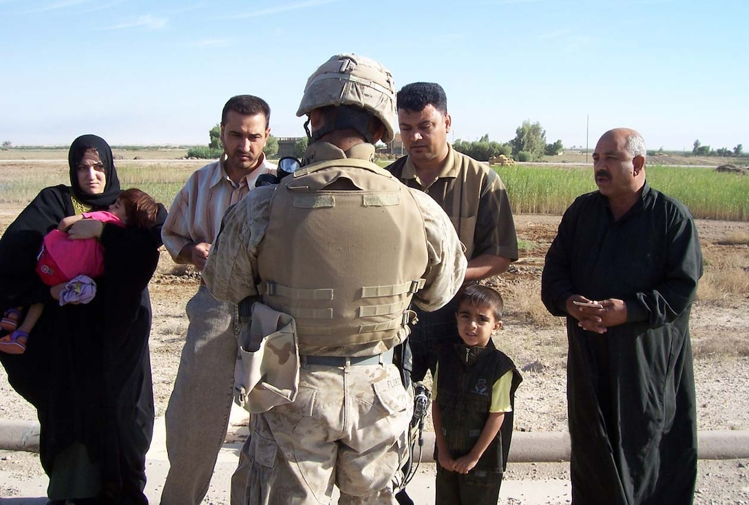 CAMP FALLUJAH, Iraq -- Lance Cpl. Juan M. Flores, a mortarman with Weapons Company, 3rd Battalion, 8th Marine Regiment stops to speak with locals using his language skills learned in the Survival Language Arabic Course he took while preparing for deployment to Operation Iraqi Freedom.  Photo Courtesy of Lance Cpl. Juan M. Flores.