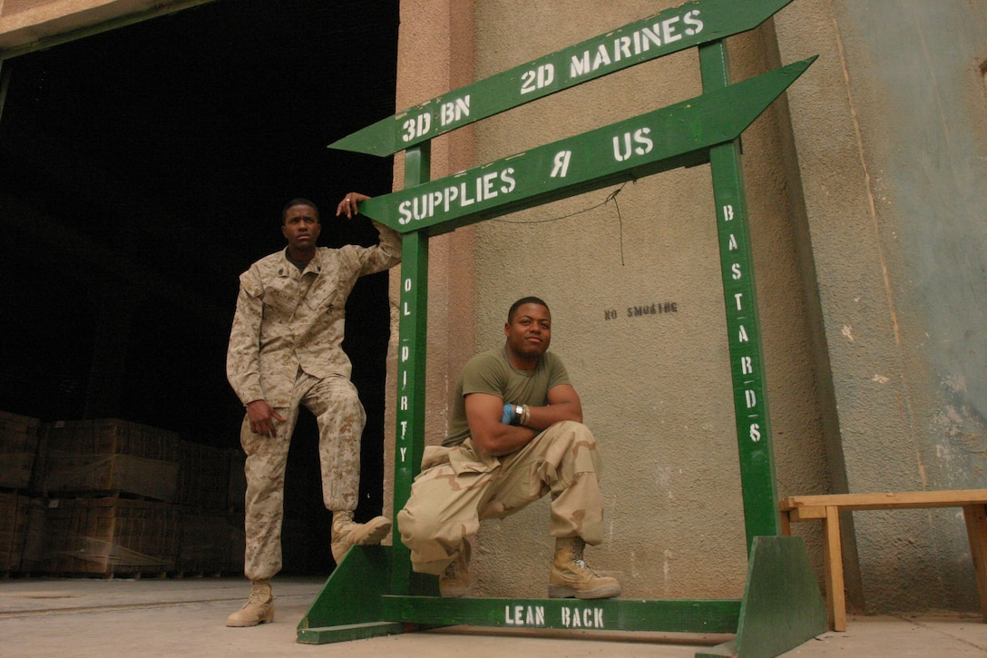 """CAMP AL QA'IM, Iraq (April 14, 2005)- Lance Cpl. Robert E. James, III, (right) and Staff Sgt. Donald R. Williams (left) both supply Marines with 3rd Battalion, 2nd Marine Regiment, Regimental Combat Team-2 stand with their now infamous """"Supplies R' Us"""" sign here. James, a Roanoke, Va., native joined the Marines after his father presented the option to him. The 2003 William Fleming High School gradute describes his high school years as his troubled times and thanks the Corps for his turn around. Official U.S. Marine Corps photo by Lance Cpl. Lucian Friel (RELEASED)"""