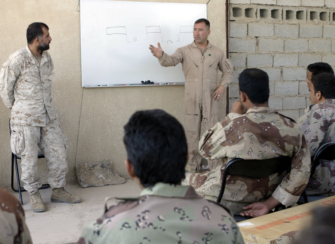 CAMP BAHARIA, Iraq - Staff Sgt. George Ferguson, 1st Battalion, 6th Marine Regiment's motor transport maintenance chief, lectures a class of Iraqi soldiers here June 30.  1st Battalion, 6th Marine Regiment motor transport personnel instructed these soldiers on topics such as how to organize a logistics convoy and perform basic preventive maintenance on their vehicles, as part of the battalion's ongoing effort to train the Iraqi Security Forces.