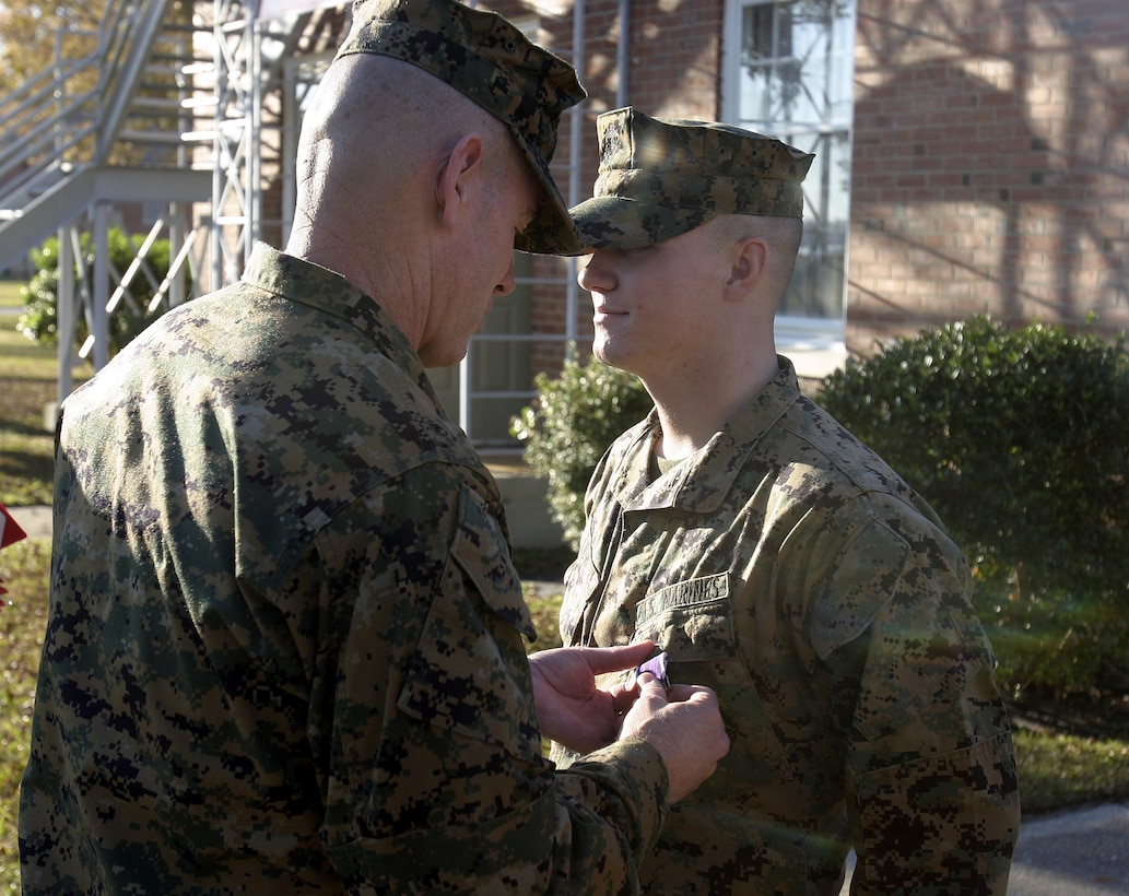 MARINE CORPS BASE CAMP LEJEUNE, N.C. - Lance Cpl. Brandon Love, an infantryman with 2nd Battalion, 2nd Marine Regiment, is presented his Purple Heart Medal here Nov. 30.  The 19-year-old Charlottesville, Va. native suffered shrapnel wounds and busted eardrums when an improvised explosive device detonated near his convoy while he and his unit had been conduction combat operations in Iraq's Al Anbar province in September.