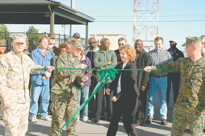 Brigadier Gen. James Flock, the Assistant Deputy Commandant of Facilites and Services for Headquarters Marine Corps, cuts the ribbon on the new Joint Hazardous Materials Center. Major Robert Wiser, left, Marine Aviation Logistics Squadron 31 aviation supply officer, and Capt. A.J. Brooks, station supply officer, hold the ribbon while Alice Howard, Natural Resources Environmental Affairs officer, looks on.