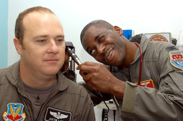 DYESS AIR FORCE BASE, Texas -- Col. (Dr.) Victor Folarin looks into Capt. Justin LeMire's ears during an examination.  Dr. Folarin immigrated to the United States from Nigeria at 20 years old to become a doctor.  Since then, he has earned five college degrees and has been an Air Force doctor since 1993.  He is the outgoing commander of the 7th Aeromedical/Dental Squadron, and Captain LeMire is a 9th Bomb Squadron resource adviser.  (U.S. Air Force photo by Airman 1st Class Kiley Olds)