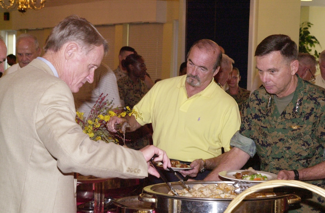 MARINE CORPS BASE CAMP LEJEUNE, N.C. - Les Palm (far left), director of the Marine Corps Association, Quantico, Va., and Assistant Commandant of the Marine Corps Gen. William L. Nyland (right) share kind words as they fill their plates during a luncheon held at the Paradise Point Officer's Club July 28.Nyland attended the luncheon to talk with active duty service members, retired Marines, family members and MCA representatives about the past, present and future of the Marine Corps. (Official Marine Corps photo by Lance Cpl. Matthew K. Hacker)