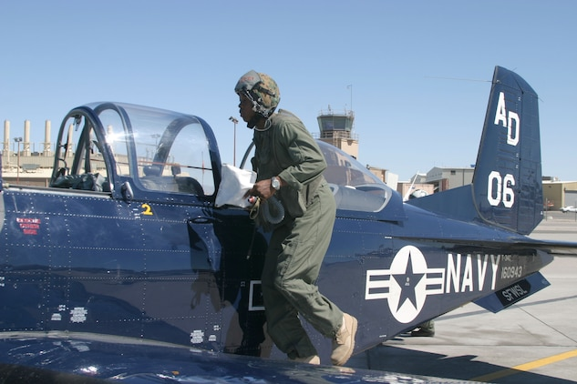 Cpl. Anthony Guas Corporal  Marteze Moore, an intelligence analyst with Marine Fighter Attack Squadron 251, mounts a T-34 aboard Naval Air Station Fallon, Nev., before taking a backseat ride, June 29. Moore received a backseat ride as a reward for becoming the Non-Commissioned of the Quarter, June 13.