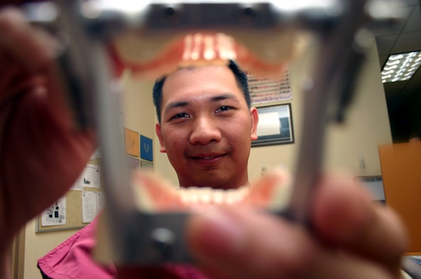 SHEPPARD AIR FORCE BASE, Texas -- Airman 1st Class Michael Dizon exams a model of teeth.  He was a dentist in the Philippines, but enlisted in the Air Force to become a dental technician.  He is working toward becoming an officer and is currently assigned to the 381st Training Squadron here.  (U.S. Air Force photo by Airman 1st Class Jacque Lickteig)