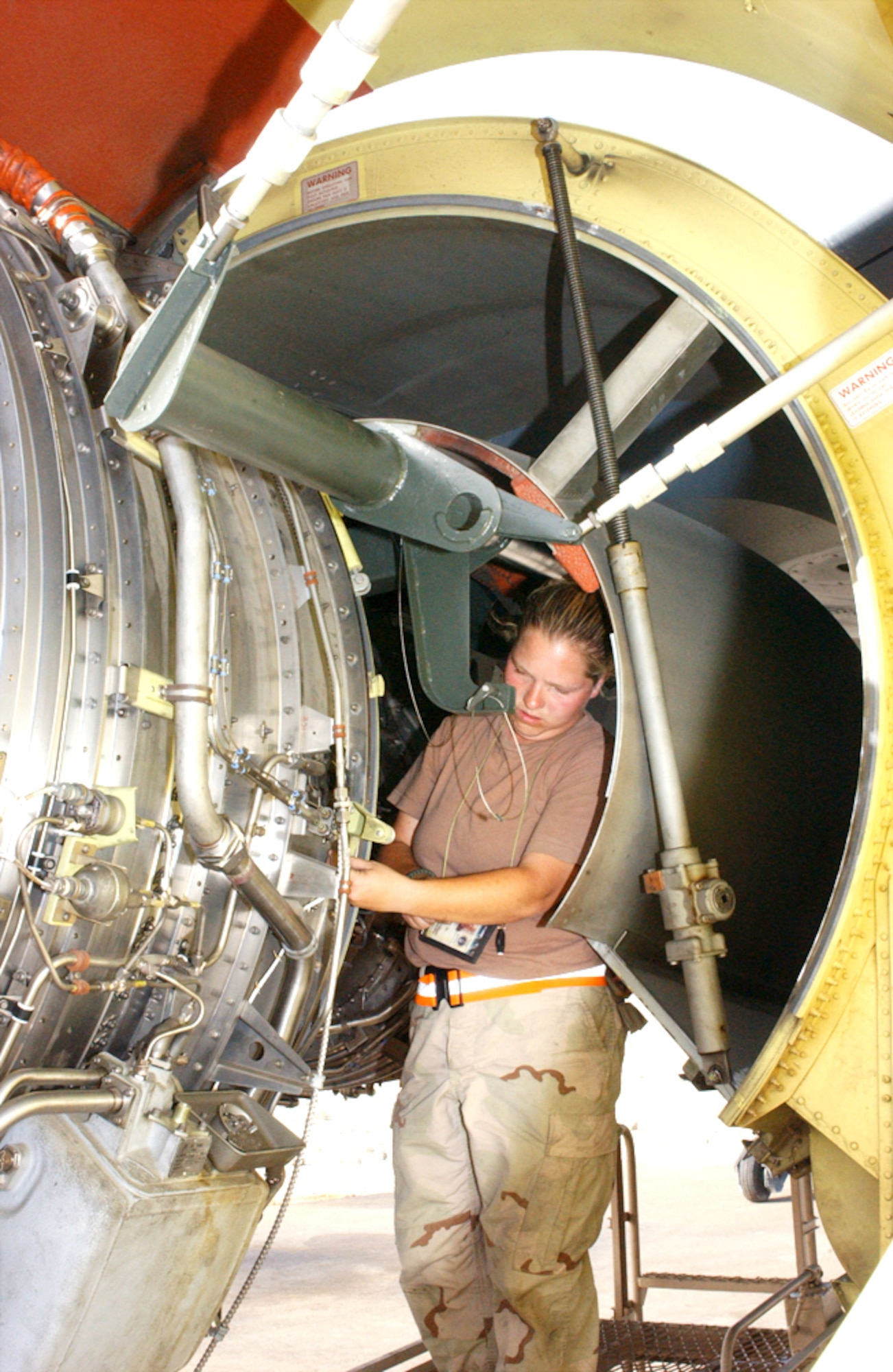 SOUTHWEST ASIA -- Senior Airman Abby Hernandez reconnects components of a KC-135 Stratotanker engine that was just installed.  KC-135 engines are very reliable and rarely have to be swapped.  Airmen at a forward-deployed location recently had to replace an engine on two KC-135s in the span of about a week.  Airman Hernandez is deployed with the 380th Expeditionary Aircraft Maintenance Squadron.  (U.S. Air Force photo by Airman 1st Class Bruce Hedrick)