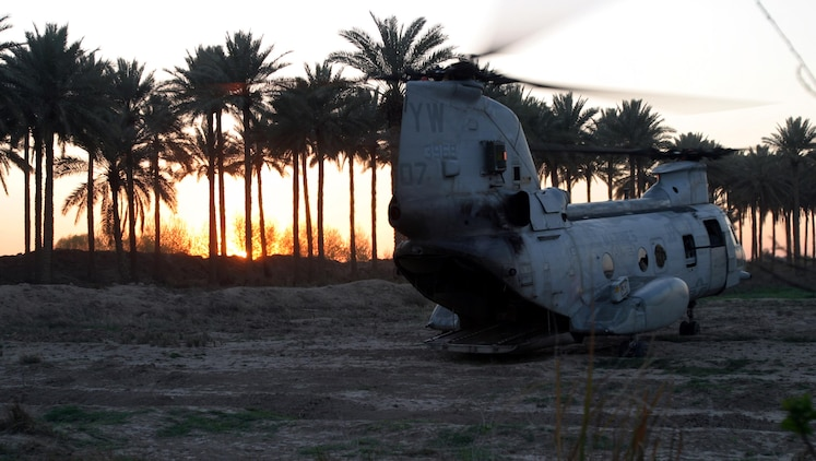 BAGHDAD, Iraq -- (Mar. 19, 2005) -  A CH-46E Sea Knight helicopter with the 15th Marine Expeditionary Unit (Special Operations Capable) sits at a Bravo Company's patrol base as the sun sets behind a palm grove in Baghdad farming community. The 15th Marine Expeditionary Unit (Special Operations Capable) is conducting security and stabilization operations in the Greater Baghdad area.