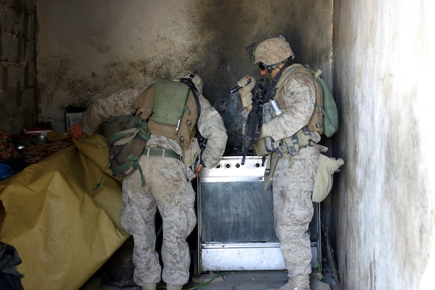 BAGHDAD, Iraq -- (March 30, 2005) - Cpl. Gary Xavier (right), 23, a native of Reno, Nev., and Lance Cpl. Matthew K. Baughman, 22, a native of Hutchinson, Kan., both infantry men with A Co., Battalion Landing Team 1/1, search an Iraqi kitchen for anything out of the ordinary during a patrol here. BLT 1/1, attached to the 15th Marine Expeditionary Unit (Special Operations Capable), is currently conducting security and stabilization operations in the Greater Baghdad area. (Official USMC photo by Lance Cpl. Thomas J. Grove)