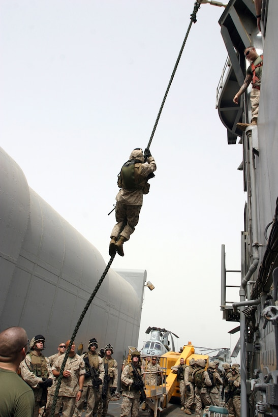 A Marine from 1st Platoon, Fox Company, Battalion Landing Team 2nd Bn., 8th Marines, 26th Marine Expeditionary Unit (Special Operations Capable) slides down a rope suspended nearly 20 feet from the flight deck of the USS Ponce (LPD-15) the morning of May 4.  These Marines spent as much time sharpening their combat skills aboard ship as they support the Global War on Terror.  (USMC Photo by: Sgt. Roman Yurek)  (Released)