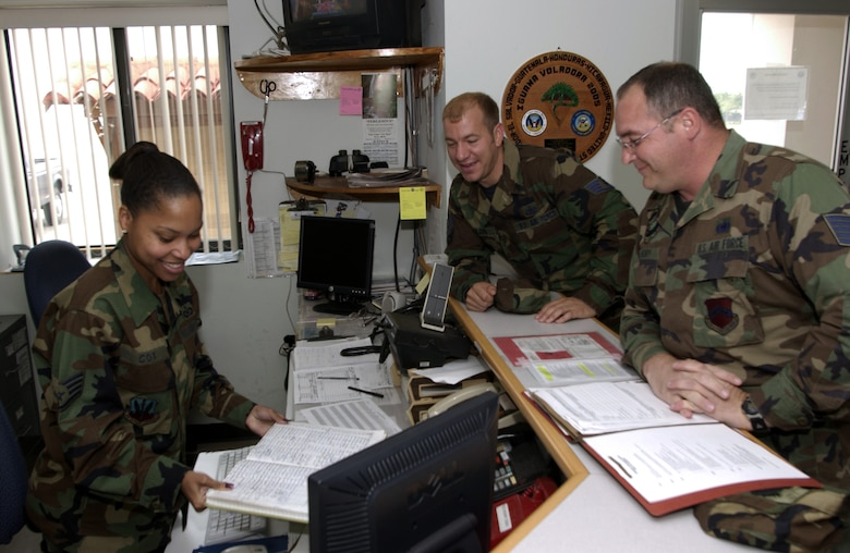 SOTO CANO AIR BASE, Honduras -- Staff Sgt. Michelle Cox processes a line badge for Tech Sgt. Marc Henry (right).  Sergeant Henry, a reservist on a 120-day deployment to the base, is replacing Staff Sgt. Charles Wilson (center) at Joint Task Force-Bravo.  Sergeant Cox is the airfield management training chief here.  (U.S. Air Force photo by Master Sgt. Lono Kollars)