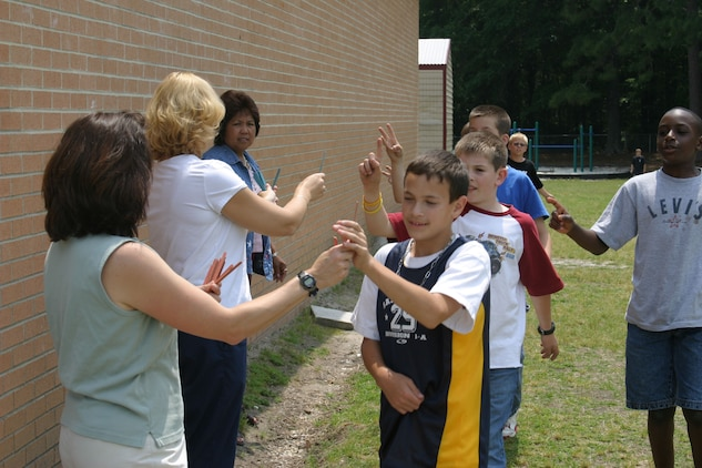 Cpl. Micah Snead Bolden Elementary School teachers and staff hand out lap sticks to students, May 10. The schools 4th, 5th and 6th graders have logged more than 6,000 miles since the walking club took its first steps Sept. 7.