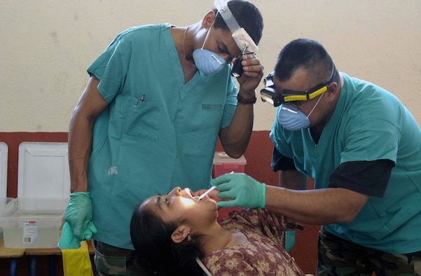 GUATEMALA -- Lt. Col. (Dr.) Gene Gaspard (left) and Tech. Sgt. Ray Salazar give a dental examine to a Guatemalan girl.  Airmen from the Air Force Reserve Command medical community deployed here for a medical readiness training exercise.  During the 10-day deployment, the medical teams treated nearly 1,000 people a day.  Sergeant Salazar and Dr. Gaspard are assigned to the 710th Medical Squadron at Offutt Air Force Base, Neb.  (U.S. Air Force photo by Master Sgt. Ruby Zarzyczny)