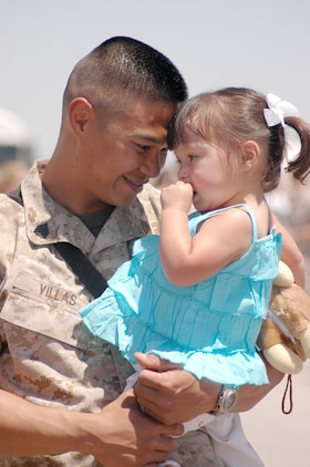 Sgt. Fred Villas, Marine Aviation Logistics Squadron-13 hydraulics mechanic, holds his daughter Emilie Villas, 2, May 19 at Marine Attack Squadron-311's hangar after a six-month deployment to Iraq.