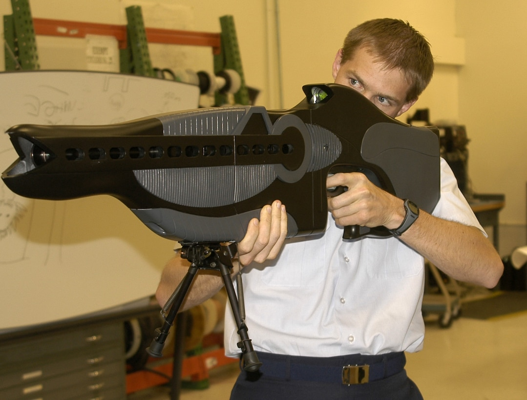"""KIRTLAND AIR FORCE BASE, N.M. (AFPN) -- Capt. Drew Goettler demonstrates the Personnel Halting and Stimulation Response, or PHaSR, a non-lethal illumination technology developed by the laboratory's ScorpWorks team. The technology is the first man-portable, non-lethal deterrent weapon intended for protecting troops and controlling hostile crowds. The laser light used in the weapon temporarily impairs aggressors by illuminating or """"dazzling"""" individuals, removing their ability to see the laser source. (U.S. Air Force photo)"""
