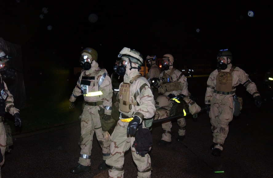 Members of the 352nd Special Operations Group perform a litter drill in full chemical warfare ensemble. The Ability to Survive and Operate is a major graded portion of the inspection.