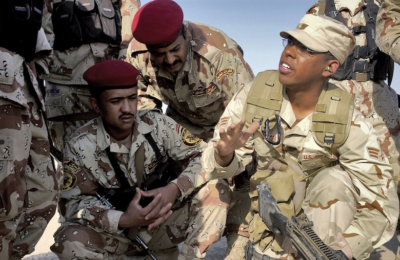 AD DIWANIYAH, Iraq -- Iraqi Soldiers listen intently as Senior Airman Patrick Dixon instructs on loading procedures of an M-249 Squad Assault Weapon.  Airman Dixon is deployed from the 1st Combat Camera Squadron at Charleston Air Force Base, S.C. (U.S. Air Force photo by Capt. Mark Harper)
