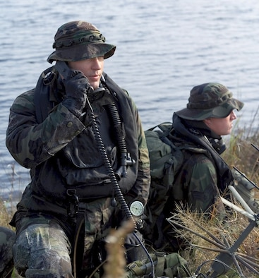 Air Force Combat Controllers make a call to aircraft using thier radios after having penetrate a Florida shoreline with tactical underwater breathing equipment during a training event.