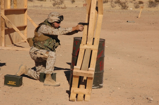 Master Sgt. Shawn Stevens, Marine Air Control Squadron 1 radar technician and native of Sequin, Wash., takes aim and fires from behind an oil drum and bench barricade at the enhanced marksmanship program range on the Barry M. Goldwater Range located southeast of the air station Nov. 17. Marines like Stevens were forced to negotiate the obstacle course, firing from behind objects at ranges from 15 to 50 yards, while carrying ammo cans full of rocks to simulate carrying ammunition on the battlefield.