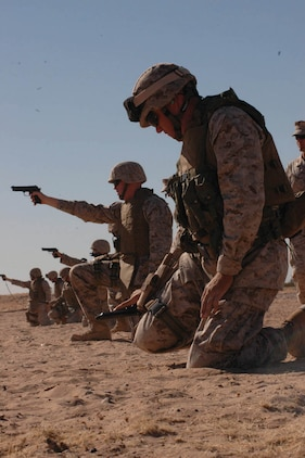 Master Sgt. Shawn Stevens (right), Marine Air Control Squadron 1 radar technician and native of Sequin, Wash., performs remidial action on his M-9 pistol during known-distance practice at the enhanced marksmanship program range on the Barry M. Goldwater Range located southeast of the air station Nov. 17. Marines were taught ways to perform remidial action on their weapons one-handed in case they are ever injured in a combat environment. Training lasted six days, preparing the MACS-1 security company Marines for a deployment to Iraq early next year. Training included both the M-9 and the M-16A2 service rifle. Marines firing on the EMP course trained for some of the conditions that they will encounter overseas.