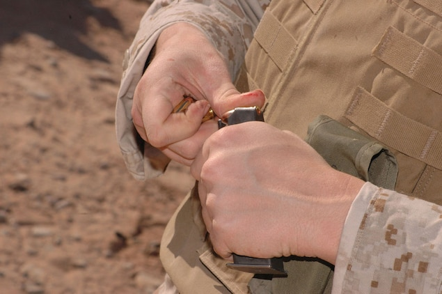First Lt. Rachel Odom, Marine Air Control Squadron 1 legal officer and native of Farmerville, La., loads rounds into the magazine of an M-9 9mm pistol at the enhanced marksmanship program range on the Barry M. Goldwater Range located southeast of the air station Nov. 17. Odom will also serve as a platoon commander during the deployment.