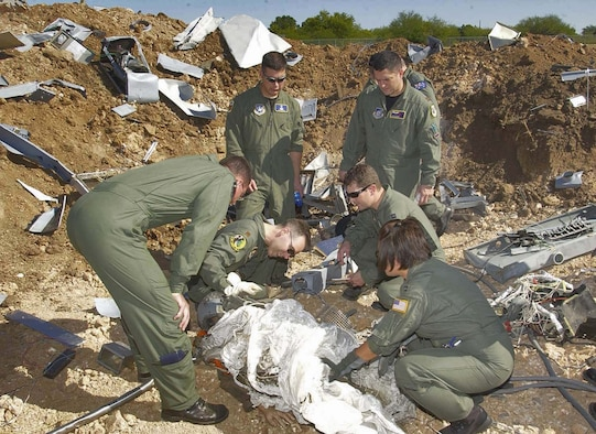 """BROOKS CITY-BASE, Texas (AFPN) -- Students of the Aircraft Mishap Investigation and Prevention course at the U.S. School of Aerospace Medicine sift through the """"wreckage"""" at a mock aircraft crash site.  The site is used in field exercises to give students a realistic idea what an actual site might be like. The course recently underwent changes, moving from a primarily lecture-based format to a more hands-on, problem-based learning approach. (Air Force photo by Tech. Sgt. Alfonso Ramirez)"""