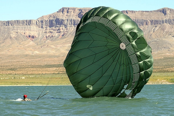 NELLIS AIR FORCE BASE, Nev. -- Senior Airman Christopher Harding gathers his parachute after landing in Lake Mead. A pararescueman with the 55th Rescue Squadron here, he had just jumped out of a C-130 Hercules as part of a rescue and recovery exercise. The squadron has 16 pararescueman who were involved in recovery missions during Hurricane Katrina and Rita. (U.S. Air Force photo by Julie Ray)