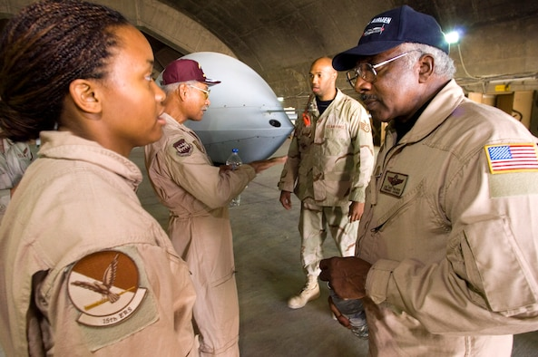 BALAD AIR BASE, Iraq (AFPN) -- Staff Sgt. Kimberly Farrell (left) talks to Tuskegee Airman retired Col. Dick Toliver (right), while Staff Sgt. Avery Ware (back right) chats with retired Lt. Col Robert Ashby (back left) here. The Tuskegee Airmen are here to meet deployed 332nd Expeditionary Operations Group Airmen and observe operations. The Army created the Tuskegee Airmen unit in 1941.  (U.S. Air Force photo by Master Sgt. John E. Lasky)
