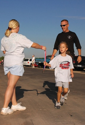 Capt. Brian Bell, Marine Wing Support Squadron 371 Support Company commander, and his daughter Georgia cross the finish line at the 10th-annual Red Ribbon Week walk/run event at West Wetlands Park Oct. 29. Drug Education for Youth kids, Marines, family members and members of the Yuma community gathered for the event to promote drug-free, healthy lifestyles.