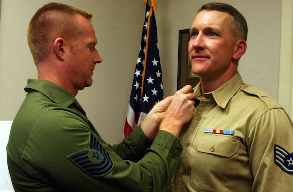 F.E. WARREN AIR FORCE BASE, Wyo. -- Tech. Sgt. Shawn Davis (left) puts the finishing touches on the vintage uniform of Chief Master Sgt. Mark Brejcha.  Sergeant Davis is wearing fatigues from the 1970s, and Chief Brejcha is wearing a Korean War-era 505 khaki shirt, worn by his father in 1954.  The sergeants are members of Living Legends, an organization dedicated to preserving and increasing awareness of the Air Force's heritage.  Airmen wear vintage uniforms at Air Force special events and share the history of the person who donated the uniform.  Sergeant Davis is the noncommissioned officer in charge of the 90th Mission Support Squadron's personnel relocation, and Chief Brejcha is the 90th Mission Support Group superintendent.  (U.S. Air Force photo by Airman 1st Class Tessa Cubbon)