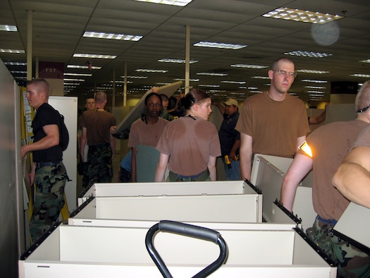 SAN ANTONIO -- Airmen from nearby Lackland Air Force Base remove modular office furniture to make room for people displaced by Hurricane Katrina. In all, 200 Airmen helped turn a 350,000 square foot office building into a living area.  (U.S. Air Force photo by Tech. Sgt. J.C. Woodring)