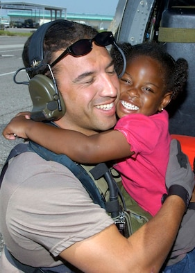 NEW ORLEANS -- A young Hurricane Katrina survivor hugs her rescuer, Staff Sgt. Mike Maroney, after she was relocated to the Louis Armstrong New Orleans International Airport, La., on Sept. 7.  Sergeant Maroney is a pararescueman from the 58th Rescue Squadron at Nellis Air Force Base, Nev.  (U.S. Air Force photo by Airman 1st Class Veronica Pierce)
