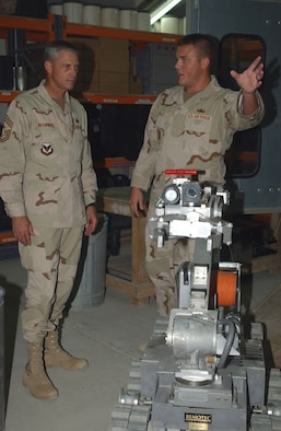 SOUTHWEST ASIA -- Airman 1st Class Joshua Mills (right) explains the capabilities of an explosive ordnance disposal robot to Chief Master Sgt. Curtis Brownhill, the command chief for U.S. Central Command. The chief is touring bases in the CENTCOM area of responsibility.  Airman Mills is assigned to the 380th Expeditionary Civil Engineer Squadron at a forward-deployed location and is from McGuire Air Force Base, N.J. (U.S. Marine Corps photo by Staff Sgt. J.J. Rodriguez)