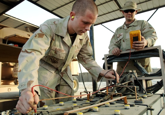 "ALI BASE, Iraq -- Senior Airmen Leslie Glandon (left) and James Suter, test voltage on a ""start cart"" used to start generators. They are assigned to the 407th Expeditionary Civil Engineer Squadron power production element. (U.S. Air Force photo by Master Sgt. Maurice Hessel)"