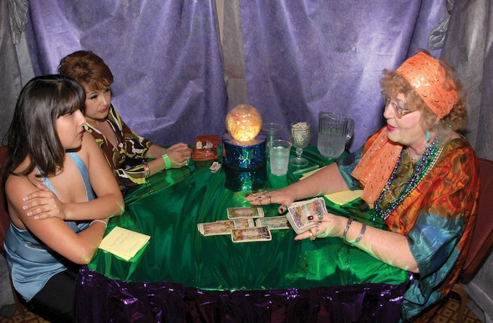 The Gypsy Woman reads a fortune in the tarot cards to mother and daughter Mary and Tara Verdugo Friday during the Marine Corps Community Services annual Mardi Gras party at the Sonoran Pueblo.