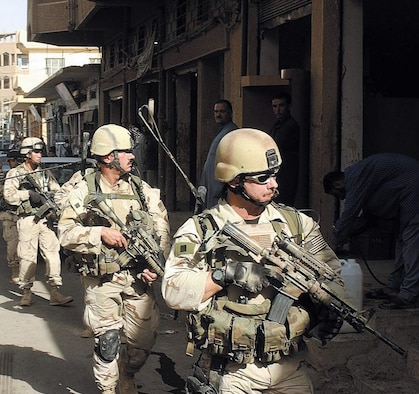 Enlisted tactical air controllers from the 14th Air Support Operations Squadron accompany the Army's 82nd Airborne Division on a foot patrol through an arms market in Iraq. (U.S. Air Force photo/14th Air Support Operations Squadron)