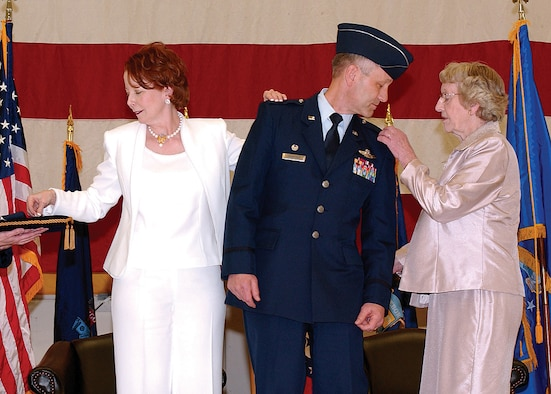 MCCHORD AIR FORCE BASE, Wash., - Beth Crabtree, left, and Ruth Crabtree right, pin on Brig. Gen. Eric Crabtrees stars during his promotion ceremony April 1.  General Crabtree is the commander of the 446th Airlift Wing.